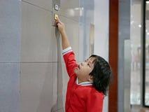 Peu bébé asiatique, 3 années, l'atteignant pour distribuer pour essayer de pousser le bouton d'ascenseur photos stock