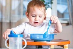 Peu bébé garçon apprenant à manger avec une cuillère lui-même à la table d'enfants dans la cuisine Concept d'aliment pour bébé sa photographie stock libre de droits