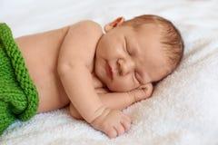 Peu bébé garçon nouveau-né dormant dans la couverture blanche, se trouvant sur le lit photographie stock libre de droits