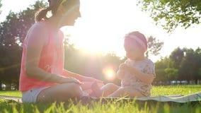 Peu bébé s'asseyant avec sa mère sur l'herbe verte en été clips vidéos
