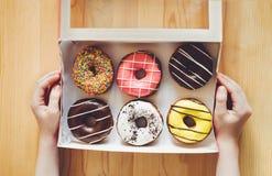 Peu badine des mains tenant la boîte avec le dessert doux de beignet photos stock