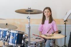 Peu batteur caucasien de fille jouant le kit elettronic de tambour et shuoting Les filles de l'adolescence ont l'amusement jouant images libres de droits