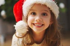 Peu belle fille avec le chapeau rouge de Santa photos stock