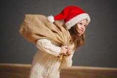 Peu belle fille avec le chapeau rouge de Santa image stock