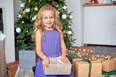 Peu belle fille avec les cheveux bouclés blonds considère ses cadeaux dans la perspective de l'arbre de Noël Noël photographie stock libre de droits