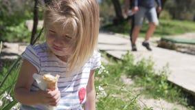 Peu blonde de fille mange la crème glacée dans une tasse de gaufre un jour chaud banque de vidéos