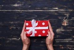 Peu boîte-cadeau pointillé gardant par les mains femelles Photos libres de droits