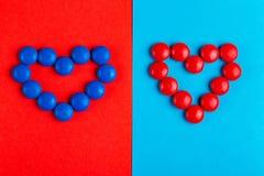 Peu chocolat vitré bleu et sucreries rouges formées dans le coeur photographie stock