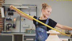 Peu concept de constructeur Tiré d'une fille de 10 ans dans l'usine jouant avec le ruban métrique jaune de construction et banque de vidéos
