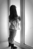 Peu a dérangé la fille s'asseyant sur le rebord de fenêtre image libre de droits