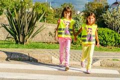 Peu d'école primaire badine traverser la rue portant un gilet avec le sinus d'arrêt là-dessus images stock