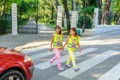 Peu d'école primaire badine traverser la rue portant un gilet avec le sinus d'arrêt là-dessus photographie stock