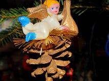 Peu d'ange se reposant sur un cône de pin Photo libre de droits