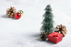 Peu d'arbre de Noël, cadeau rouge, boules et cônes sur le CCB concret Photographie stock