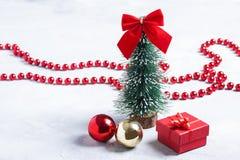 Peu d'arbre de Noël, cadeau rouge et boules sur le fond concret Image libre de droits