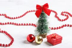 Peu d'arbre de Noël, cadeau rouge et boules sur le fond concret Photographie stock libre de droits