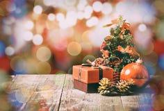 Peu d'arbre de Noël sur la table en bois et le petit boîte-cadeau, cônes de sapin Photographie stock