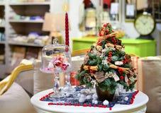 Peu d'arbres de Noël est sur la table à côté d'une bougie photographie stock libre de droits