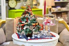 Peu d'arbres de Noël est sur la table à côté d'une bougie image stock