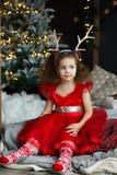 Peu d'assez fille de sourire bouclée reposant presque l'arbre de Noël avec des décorations et des présents de Noël Enfant dans la image libre de droits