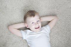 Peu d'enfant à la maison sur un tapis image libre de droits