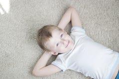 Peu d'enfant à la maison sur un tapis image stock