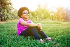 Peu d'enfant appréciant et écoutant la musique en parc vert photos stock