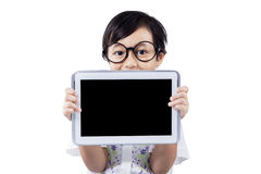 Peu d'enfant avec l'écran vide de comprimé dans le studio Photos libres de droits