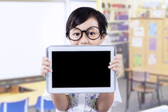 Peu d'enfant avec le comprimé dans la salle de classe Photo libre de droits