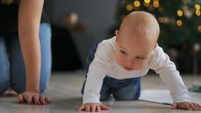 Peu d'enfant avec le jouet dans la bouche rampant sur le sofa Fermez-vous du bébé nu dans des couches-culottes marchant sur le li clips vidéos