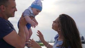 Peu d'enfant dans des mains fortes du ` s de père près de la mère, enfance heureux de nourrisson outre des parents affectueux,