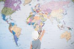 Peu d'enfant dans le chapeau de capitaine se dirigeant à la carte du monde avec la visite de direction de doigt photographie stock libre de droits