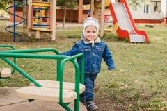 Peu d'enfant dans le costume de jeans joue sur le terrain de jeu, garçon tournant sur le carrousel photos libres de droits