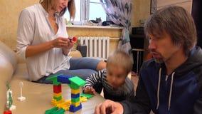 Peu d'enfant et sa maman et papa jouant avec la construction réglée à la maison ensemble tir 4k banque de vidéos