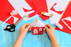 Peu d'enfant a fait un ornement de cabane dans un arbre de Noël du feutre rouge et blanc L'enfant tient l'ornement de maison de N Photos libres de droits