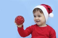 Peu d'enfant habillé comme Santa Claus montrant une babiole rouge Photo libre de droits