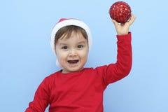 Peu d'enfant habillé comme Santa Claus montrant une babiole rouge Photographie stock libre de droits