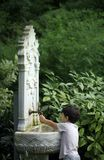 Peu d'enfant jouant avec de l'eau de fountai de classique de style de tabouret Image libre de droits