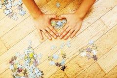 Peu d'enfant jouant avec des puzzles sur le plancher en bois ainsi que la PA Image stock