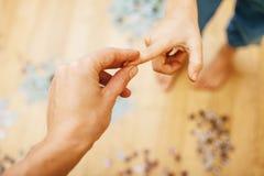 Peu d'enfant jouant avec des puzzles sur le plancher en bois ainsi que le parent, concept de personnes de mode de vie, mains affe Photographie stock libre de droits