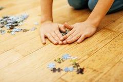 Peu d'enfant jouant avec des puzzles sur le plancher en bois ainsi que le parent, concept de personnes de mode de vie, mains affe Photo libre de droits