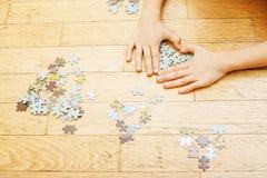 Peu d'enfant jouant avec des puzzles sur le plancher en bois ainsi que le parent, concept de personnes de mode de vie, mains affe Photographie stock