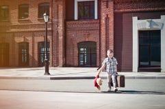 Peu d'enfant juge la valise et le jouet d'ours de nounours traversant la rue ensoleillée Photos stock