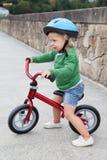 Peu d'enfant montant son vélo vers le bas Photo libre de droits