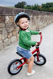 Peu d'enfant montant son vélo vers le bas Image libre de droits