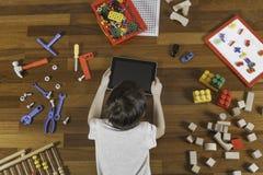 Peu d'enfant se trouvant et jouant avec la tablette Sort de jouets autour de lui sur le plancher en bois Vue supérieure Photo libre de droits