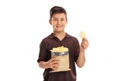 Peu d'enfant tenant un sac des pommes chips Image stock