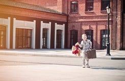 Peu d'enfant tient la valise et le jouet d'ours de nounours et le de plain-pied Photo stock