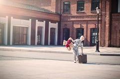 Peu d'enfant tient la valise et le jouet d'ours de nounours et le de plain-pied Image stock