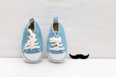Peu d'espadrilles de bleus layette pour le garçon et les moustaches sur un woode blanc Images libres de droits